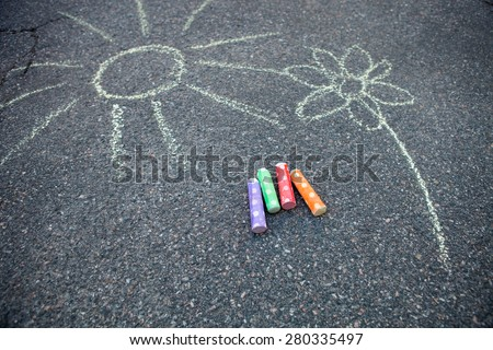 Sun and flower drawn to the ground with colorful street chalk - stock photo