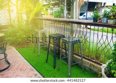 Sun beam warm light with view of empty outdoor cafe table at park, Set up table in a restaurant - stock photo