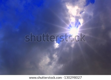 Sun beams and clouds - stock photo