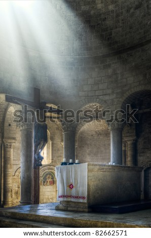 Sun beams illuminating Jesus Christ on the Cross and altar in old Monastery in Tuscany, Italy - stock photo
