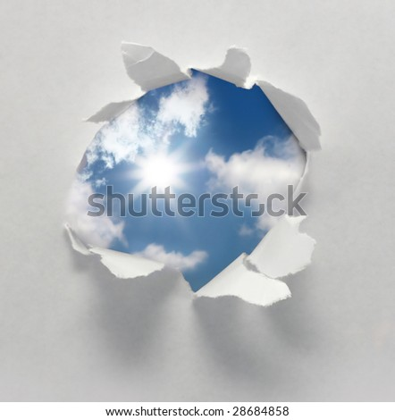 sun behind a paper hole - stock photo
