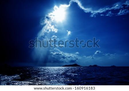 Sun bursting through dramatic skies over the ocean - stock photo