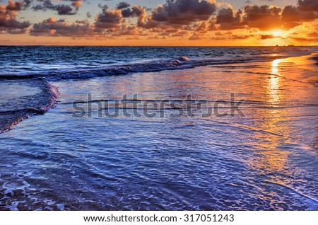 Sun casts an orange hue on the horizon, above the clear water - stock photo