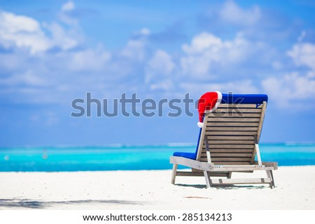 Sun chair lounge with red Santa Hat on tropical white beach and turquoise water - stock photo