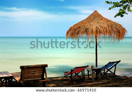 Sun chair under umbrella on a tropical sandy beach - stock photo
