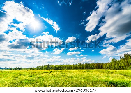 Sun comes out of cumulus clouds and illuminates a field in the forest - stock photo