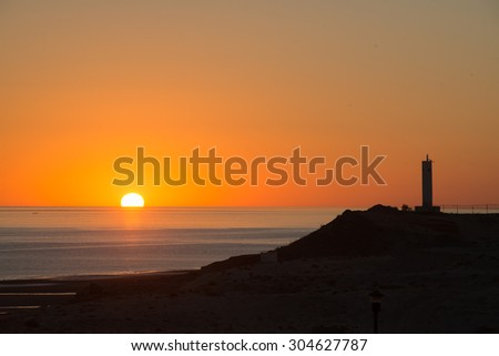 Sun coming out behind the lighthouse - stock photo