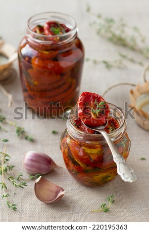 Sun dried tomatoes with herbs and sea salt in olive oil in a glass jar - stock photo