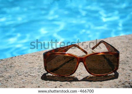 Sun glasses by the pool - stock photo