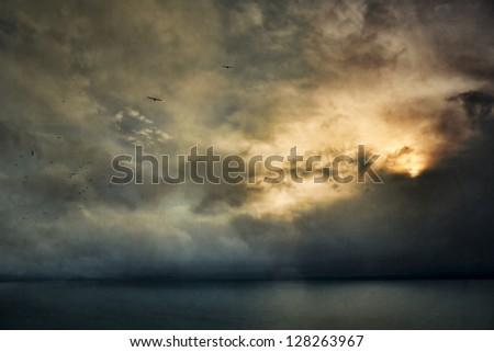 Sun glowing behind clouds over the sea with birds flying. - stock photo