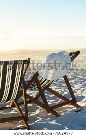 Sun hat hanging from beach chair on sand at sunset; a vacation or retirement concept - stock photo