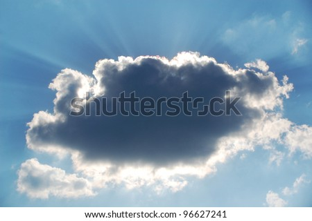 Sun hiding behind a cloud on the day sky. - stock photo