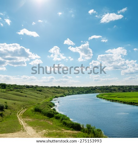 sun in blue sky with clouds over river - stock photo
