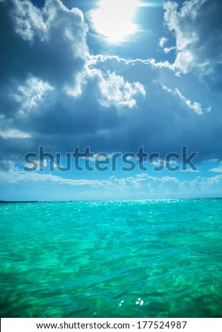 sun in the sky and beautiful waters of the caribbean sea near the saona island - stock photo
