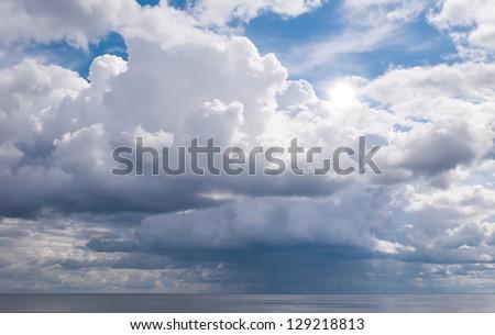 Sun is higher than a rain cloud over the sea - stock photo