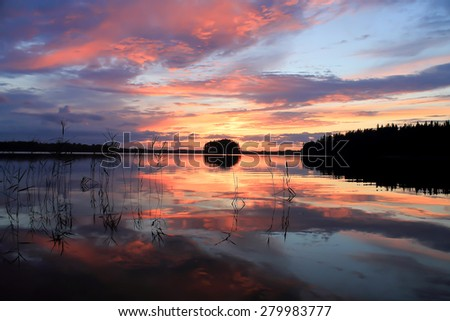 Sun is setting or rising over the lake and it's lights and clouds are reflecting in water. - stock photo