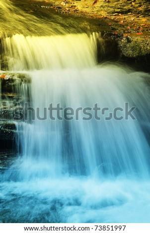 sun light over illuminated the waterfall - stock photo