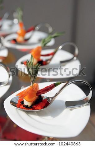 Sun-lit seafood snacks on banquet table - stock photo