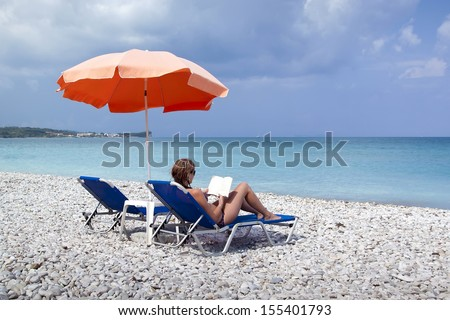 Sun lounger and umbrella on empty rock beach with reading girl - stock photo