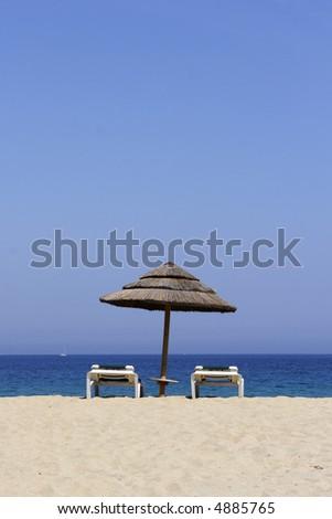 sun lounger on empty sandy beach, corsica, mediterranean - stock photo
