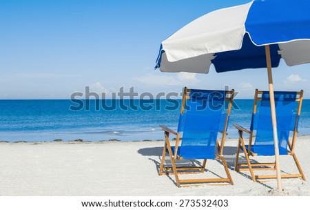 sun loungers and a beach umbrella on silver sand,  vacation concept - stock photo
