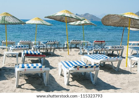 Sun loungers and wicker parasols on sandy beach in Turgutreis in the Bodrum Peninsula, Turkey. - stock photo
