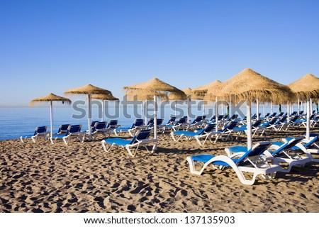 Sun loungers on a beach in Marbella, Spain, Costa del Sol, Andalusia region, Malaga province. - stock photo