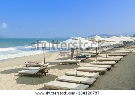 Sun lounges and beach umbrellas on a deserted beach - stock photo