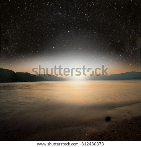 sun on a background star sky reflected in the sea. Elements of this image furnished by NASA - stock photo