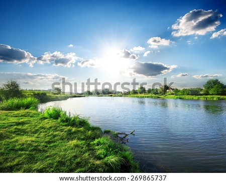 Sun over calm river in the spring morning - stock photo