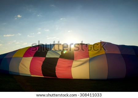 Sun peaking over the inflating envelope of a hot-air balloon - stock photo