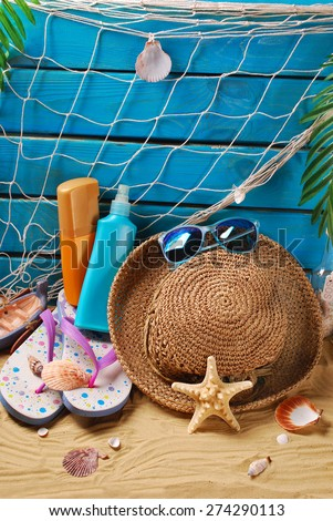 sun protection still life with suntan lotion bottles, straw hat,sunglasses,flip-flops and shells on the beach  - stock photo