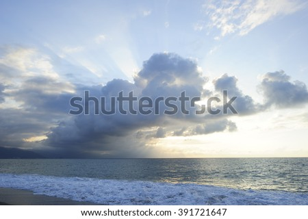Sun ray clouds is lit brightly light golden seascape with waves rolling to the shore as scattered sunbeam break through a dramatically onto the ocean horizon. - stock photo