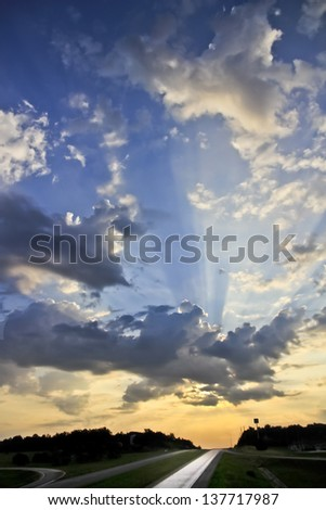 Sun rays bursting through clouds, sunrise - stock photo