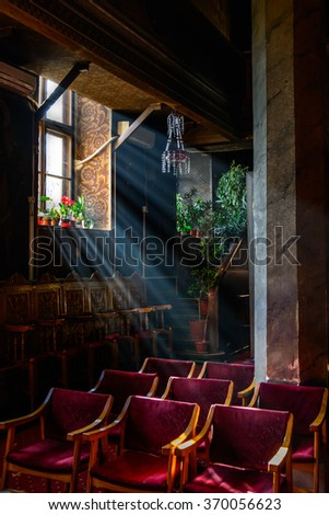 Sun rays over church window inside. A dim old church interior lit by suns rays penetrating through a colourful stained glass window with flowers over purple chairs. - stock photo
