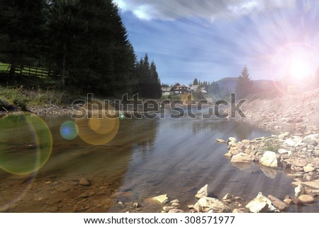 sun rays over mountain river with lens flare - stock photo