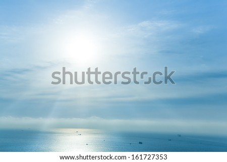 Sun rays streaming down onto the ocean. - stock photo