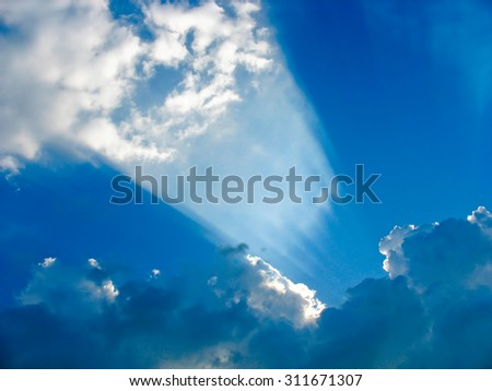 Sun rays striking through the clouds like a searchlight - stock photo