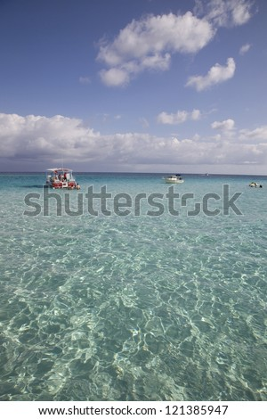 Sun reflecting on the beautiful clear tropical waters at Stingray City, Cayman Islands. - stock photo