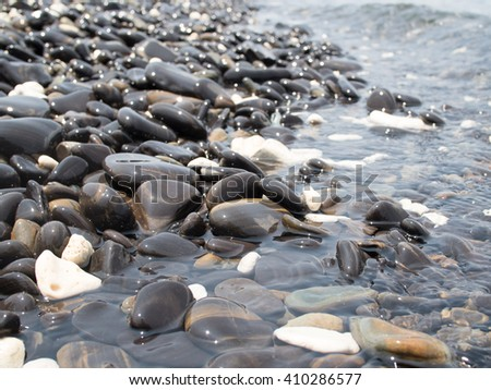 Sun reflections on pebble stones on the beach and sea water. - stock photo