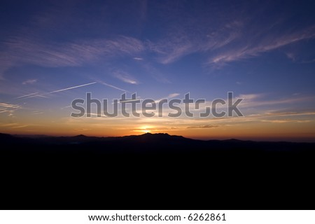 Sun rises over a distant mountain range with dark foreground for copyspace - stock photo