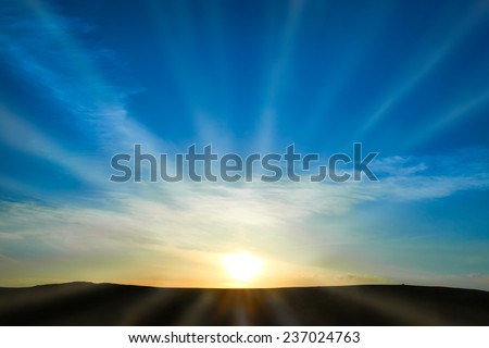 Sun rising above the land on blue sky. Nature background with sunny beams - stock photo