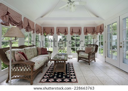 Sun room in modern home with wicker furniture - stock photo