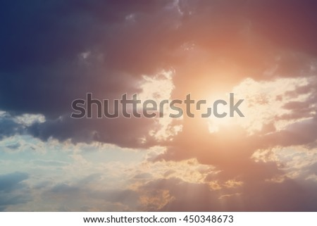 Sun's rays through the clouds at sunrise or sunset - stock photo
