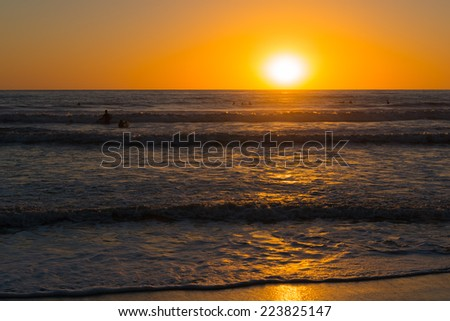 Sun set over the horizon. Pacific ocean and sky are painted in bright orange and gold colors. Waves beat against the sandy beach. - stock photo