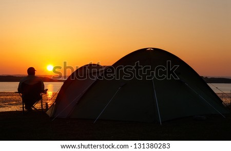 sun sets on the horizon behind a camper sitting relaxing and enjoying his camping holiday creating a silhouette of the pitched tent with him sitting beside - stock photo