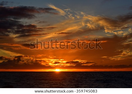 Sun setting above the Pacific Ocean, Kauai, Hawaii - stock photo