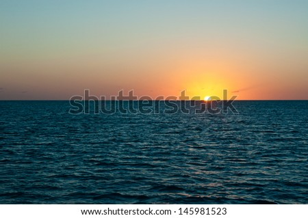 Sun setting over the ocean on a cloudless and clear beautiful night in the bahamas - stock photo