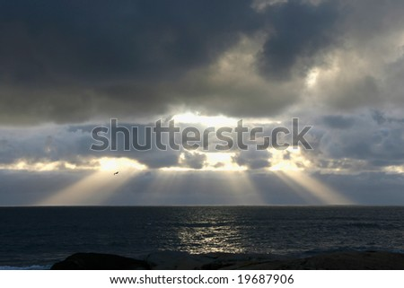 Sun setting over water with brilliant rays of light - stock photo