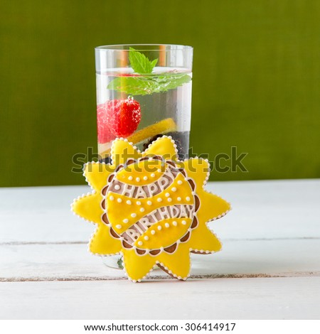 Sun shaped cookie with Happy Birthday writing and glass of glasses of delicious refreshing drink with berries. - stock photo